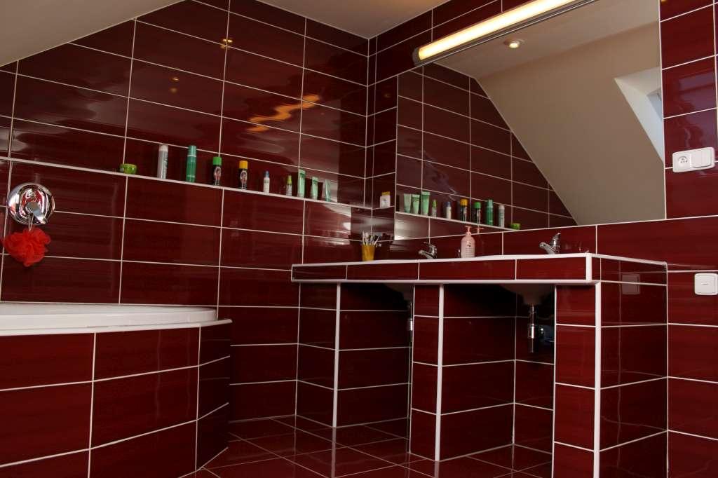 Koupelna s červenou dlažbou a obklady